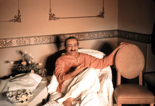 Meher Baba relaxing at the Delmonico Hotel in New York City. The white divan cover, the table-cloth and fruit bowl were provided by the Karrasch Family.