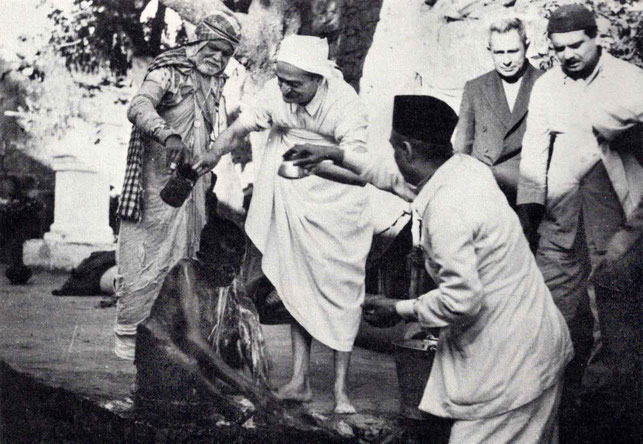 """7th November 1954 : Meher Baba at the leper colony in Pandharpur, washing a leper with Saint Gadge Maharaj  ( behind ) & Pendu Irani assisting ( right of Baba ) with Meherjee Karkaria & Eruch Jessawala. Photo by B. Panday. Courtesy of """"The Beloved""""-p.72."""
