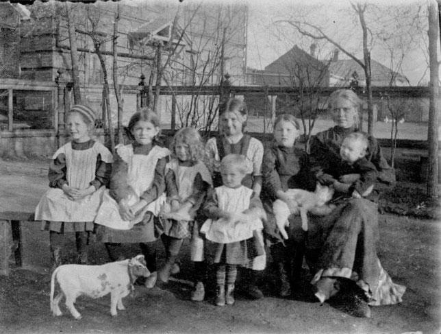 Игровая площадка в усадьбе Кушнарева, ранняя весна 1911 года. Таня Вилисова, Тося Кушнарева, Ляля и Валя (стоит) Вилисовы, дочки дворника Таля и Нюта, няня с Мишей Вилисовым.