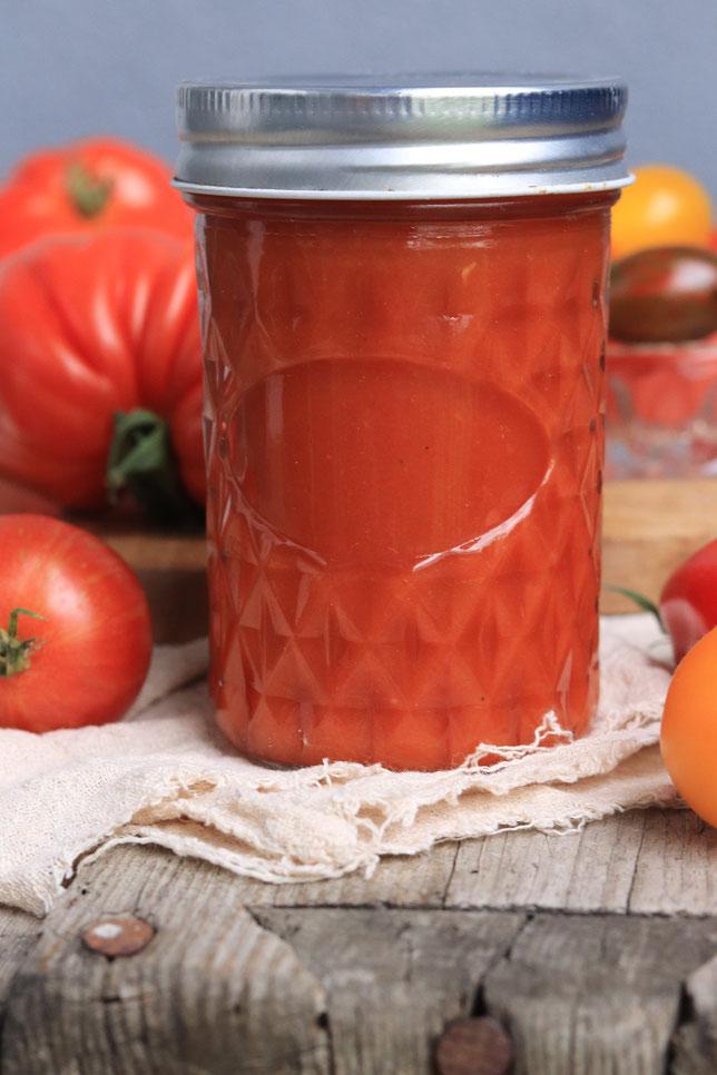 Ketchup im Glas und Tomaten
