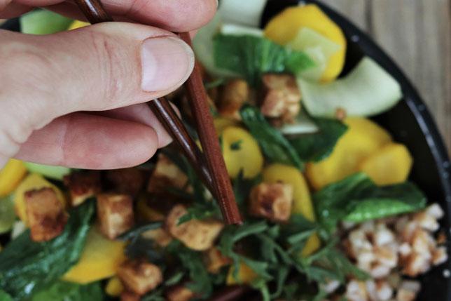 Pak Choi mit Karotten und Tofu werden mit Essstäbchen gegessen