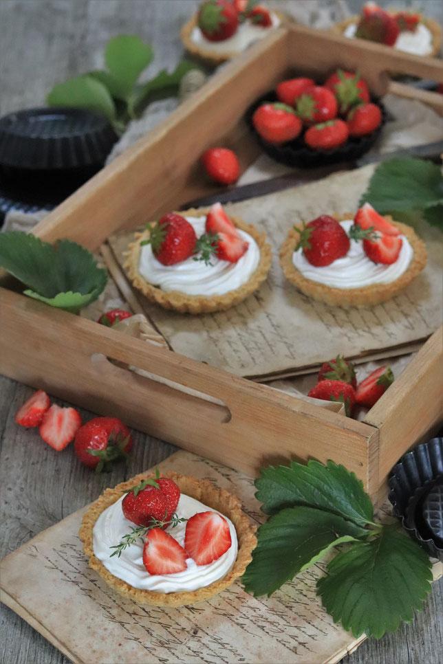 Erdbeertörtchen und Erdbeeren auf einem Tablett
