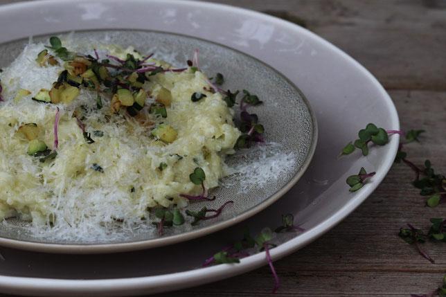 Zucchinirisotto auf einem Teller mit Kräutern garniert