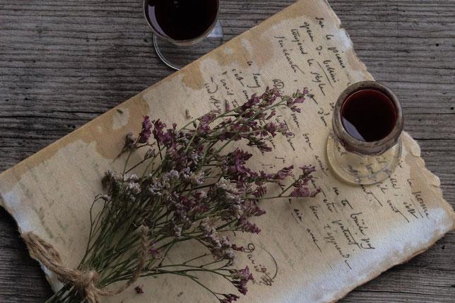 Aronialikör in einem Glas und getrocknete Blumen