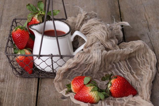 Erdbeeren und Erdbeersauce in einer Kanne