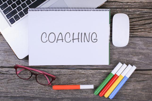 """Holztisch mit Notizblock bezeichnet """"Coaching"""", Laptop, Stifte und eine Brille"""