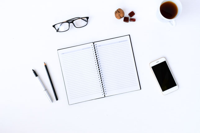Notizheft mit Stift, Brille und Handy am weißen Schreibtisch