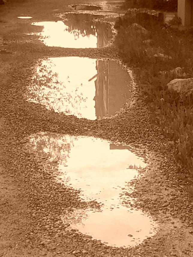 Pfützen entstehen. Verschwinden wieder. Spiegeln zwischendurch Beständiges. Wie das Leben. Dachte sie. Und ging weiter ihren ziellosen Weg.