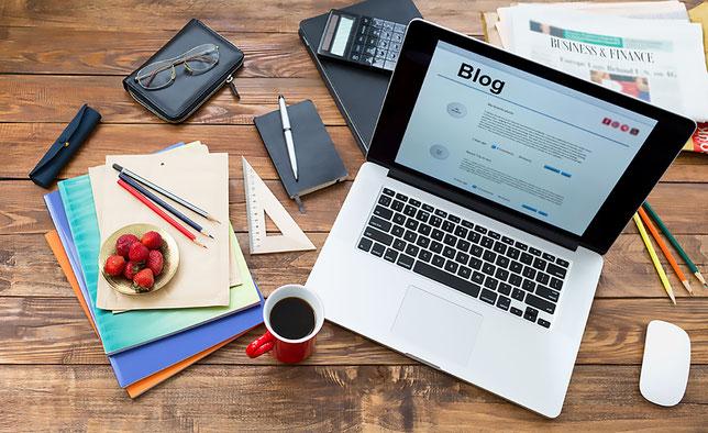Schreibtisch mit Utensilien für das Bloggen: Laptop, Notizbuch, Stiftes