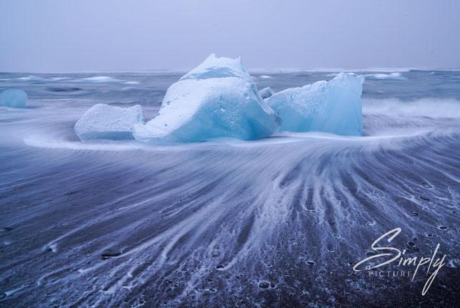 Iceland, Brandung des Meeres umspühlt einen Eisblock