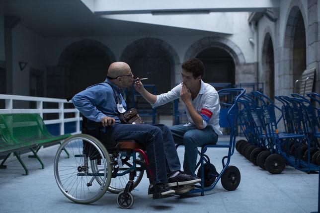 Un aide-soignant partage en cachette une cigarette avec le pèlerin paralysé dont il s'occupe (©Mars Films).