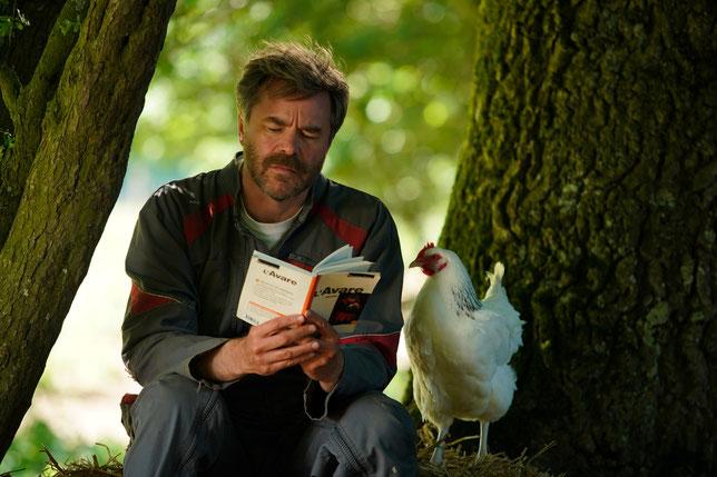 """L'agriculteur Raymond (Guillaume de Tonquédec) lit à sa poule Roxane du """"Cyrano de Bergerac"""" mais aussi d'autres textes classiques, comme ici """"L'Avare"""" de Molière (©Mars Distribution)."""