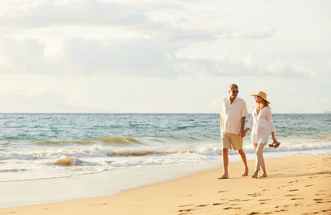 Couple walking on beach thanks to a Fee Only Investment Management Firm in East Cobb