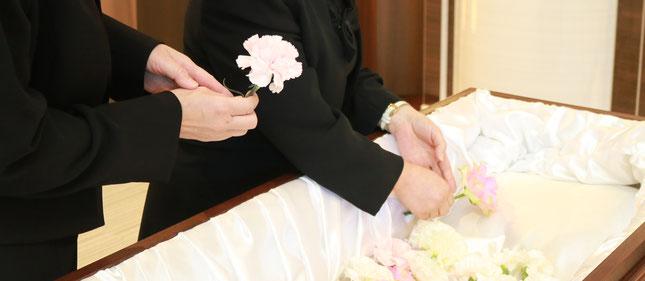家族が棺の中に花を添えている
