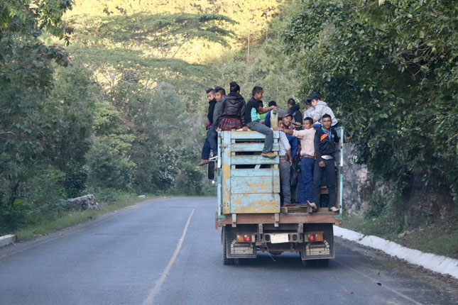 A truck full of people in the early morning heading to Coban