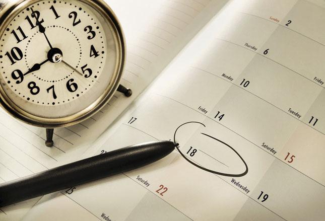 Eine Uhr, ein Kalender und ein Stift