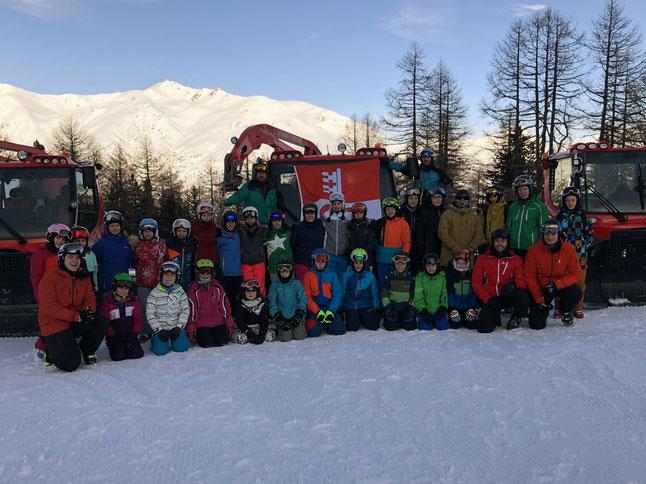 Lager Teilnehmer/innen und Leiter vor Bergkulisse und Pistenfahrzeugen