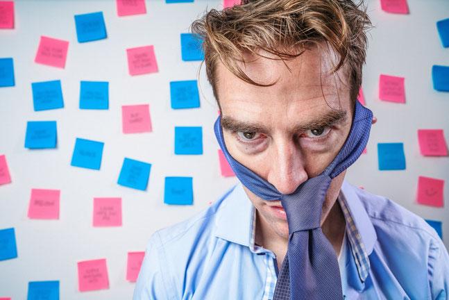 Durchgedrehter Mann mit Krawatte um den Kopf ist mit der betrieblichen Altersvorsorge überfordert