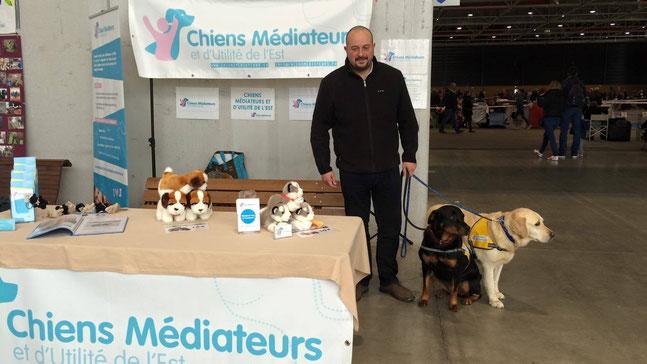 Jean-Pierre NEY assurant la promotion des CMUE lors d'un salon. A ses côtés : son chien de compagnie Nikita et un labrador en éducation au sein de l'association