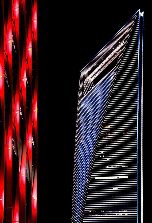Blue illuminated Shanghai World Financial Center skyscraper and a red hotel in front long-exposure at night, China, 1239x1820px