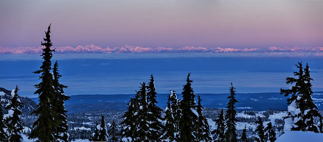 Sunsets over winter forest with Coastal Mountain Range and Georgia Strait in the background.