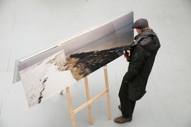 Mann mit Bild auf Staffelei von schräg oben fotografiert