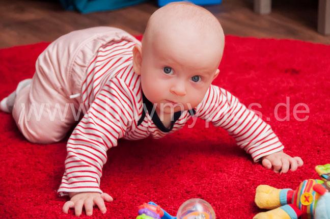 Baby versucht zu krabbeln Krabbelstube Kindertagesstätte Kindergarten Krippe Kinderkrippe Süßes kleines Kind mit großen blauen Augen Baby mit tiefen Augen