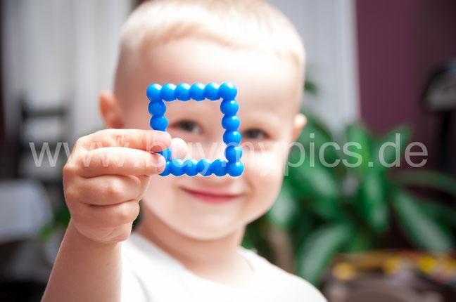 Süßer kleiner Junge spielt mit Spielzeug im Kindergarten Spielendes Kleinkind Kleiner Junge zeigt ein Spielzeug in die Kamera
