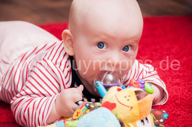 Spielendes Baby mit großen blauen Augen Babygesicht Kleines süßes Mädchen beim spielen Baby mit Spielzeugen im Mund Kleines Kind beißt am Spielzeug