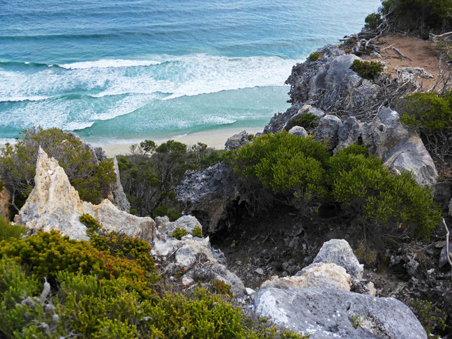 Looking down the limestone cliff face to the sea and beach below