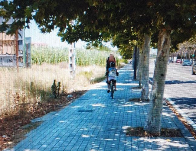 Padre y su hija de corta edad circulando por la acera con las bicis a 40 grados en València.