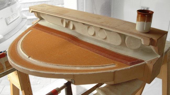 Das im Wabensandwichbau gelegte Instrumentenpanel vor dem Legen der inneren Decklage. Die Aramidwaben sind in brauner Färbung zu erkennen.