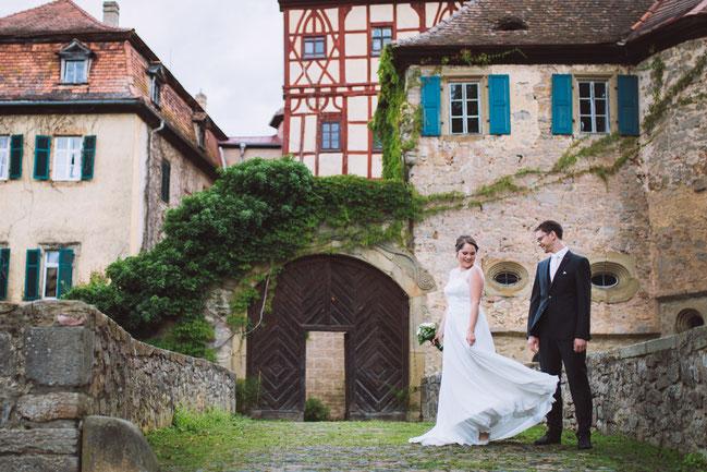 First-Look von Braut und Bräutigam vor der Kulisse des Wasserschloss Unsleben. Hochzeitsfotograf München