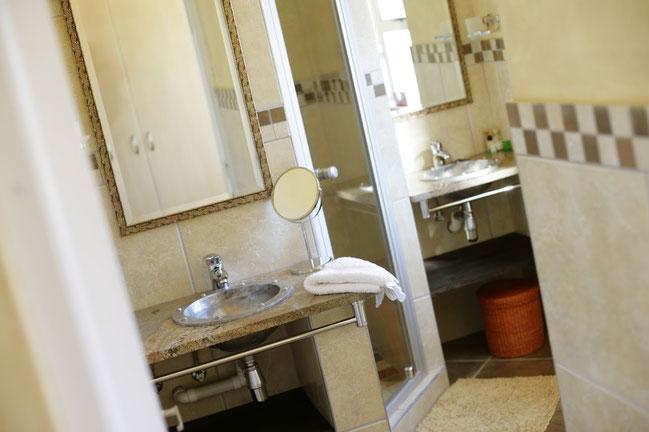 Das elegant gestaltete Badezimmer ist mit zwei Waschbecken, einer großzügigen Dusche und einem WC optimal ausgestattet.