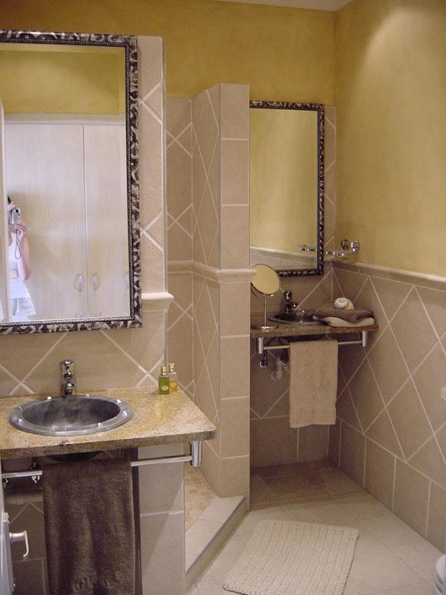 Das helle in Sandfarbe verflieste Badezimmer hat zwei Waschbecken, WC und ist mit einer ansehnlichen Dusche ausgestattet.