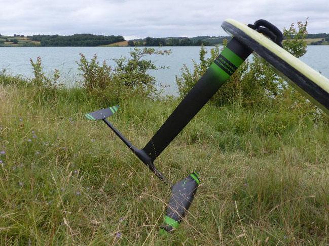 le windfoil aeromod version 2, noir et vert pomme, à la Ganguise au bord de l'eau avec son flotteur de planche à voile