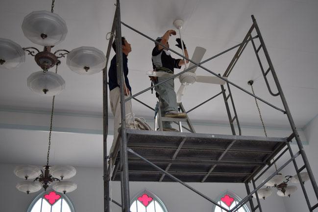 左が西大寺・花口電機(株)の花口さんです。いよいよ、エアコンの設置と同時に行われたシーリングファンが天井に付いたところ。教会の礼拝を支えてくれるはずです。