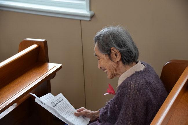 2016年10月23日(日)朝9時頃の礼拝堂にて ほかにはどなたもおられません おもてページを読み終わって、その後、内側を読み始めようとしている光子さん。しばらく、この笑顔でした。