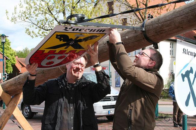 Achim Matthes (li.) und Bern Kirchhoff bringen die Embleme der Loccumer Handwerker am Maibaum an. (Foto: as/hgv)