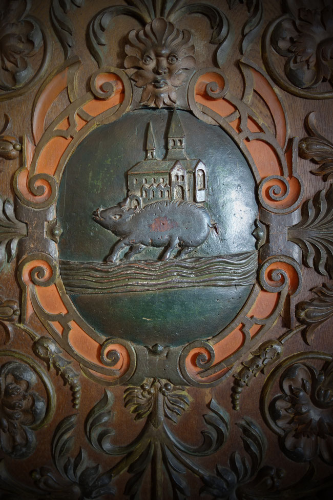 Details on a book cabinet depicting allegories of Eberbach: a church, a boar, the river