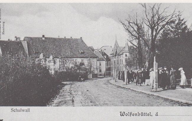 Um die Jahrhundertwende werden die jungen Damen eines Mädchenpensionats am Schulwall spazierengeführt. Im Hintergrund rechts ist ein Teil des Gebäudekomplexes der Likörfabrik MAST zu sehen. Heute befindet sich dort das ehemalige Karstadtgebäude.