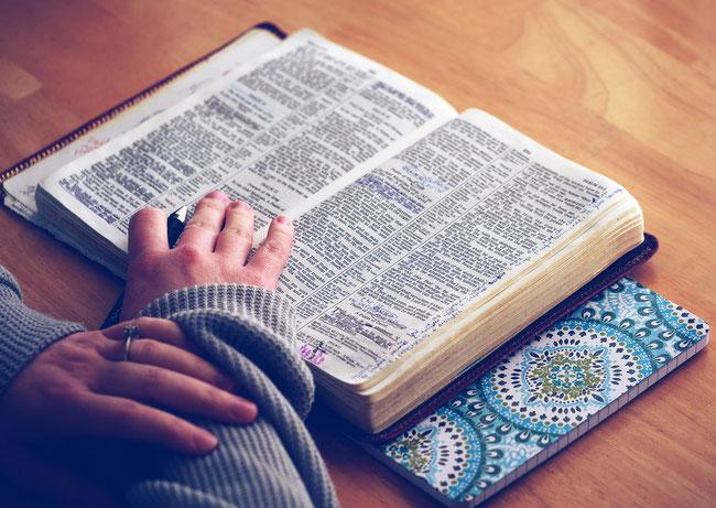 Eine Kinderhand liegt auf einer geöffneten Bibel