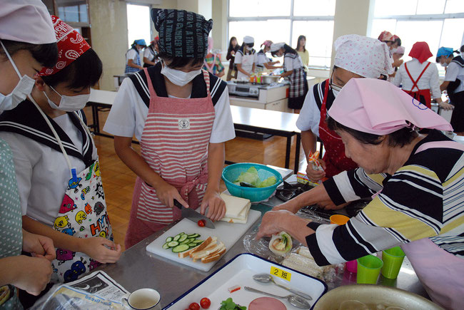 Student cuts bread and vegetable while Health Mates helps rolling bread