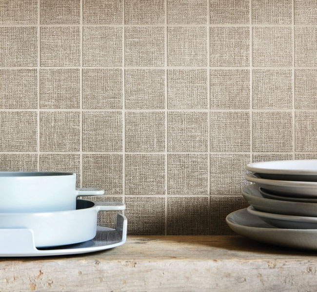 "Close-up of kitchen backsplash with tan-colored 2x2"" tile squares that have a canvas texture."
