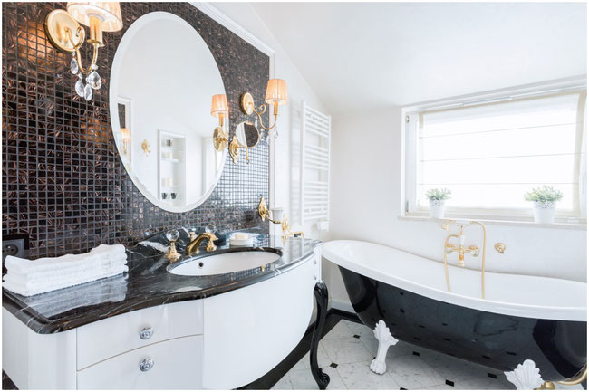 Black and white bathroom with clawfoot tub and gold fixtures.