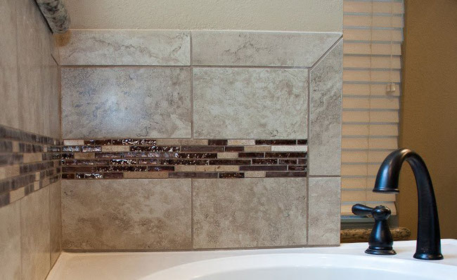 Brown porcelain tiles with a brown metallic glass and stone mosaic on a wall behind a white tub with oil rubbed bronze fixtures.