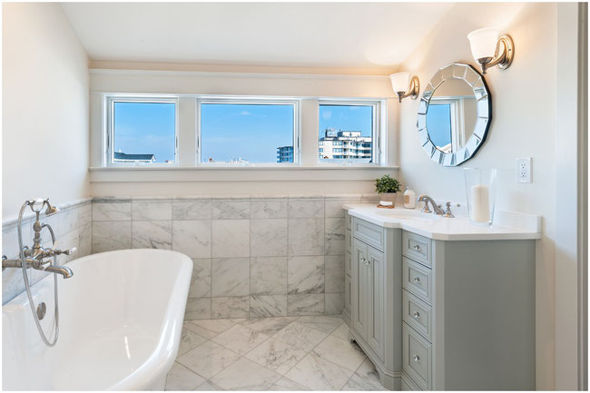 Bathroom with white clawfoot tub, Carrara marble tile floor and wainscoting, a gray vanity with white countertop, and three windows overlooking a city.