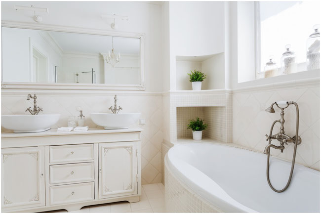 Cream and white bathroom with vessel sinks on the traditional-style vanity and a soaking tub.