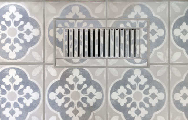 Blue, white, and grey floral-patterned cement tile cut to fit a custom floor heat vent.