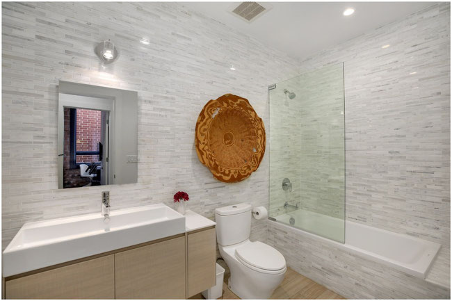 Bathroom with light blond wood floors and floating vanity, white stone mosaic walls and bathtub surround.